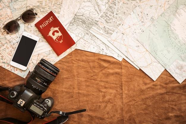 Macchina fotografica, smartphone e passaporto sul tavolo