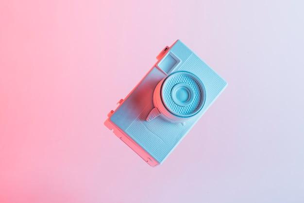 Macchina fotografica verniciata bianca contro fondo rosa