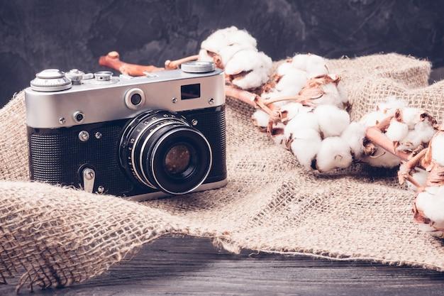 Macchina fotografica vintage e un rametto di cotone
