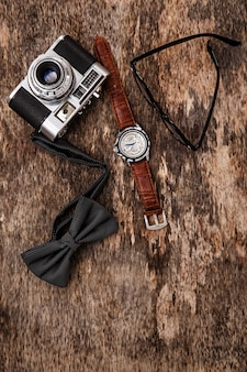 Macchina fotografica vintage, orologio da polso, occhiali e papillon