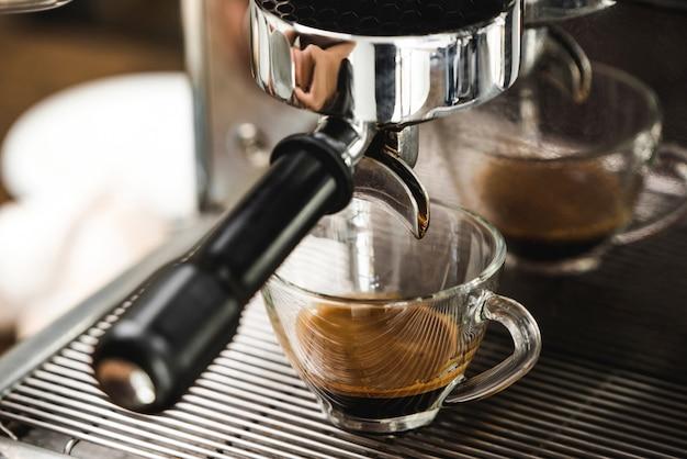 Macchina per caffè espresso che fa caffè espresso sparato in tazza di vetro trasparente
