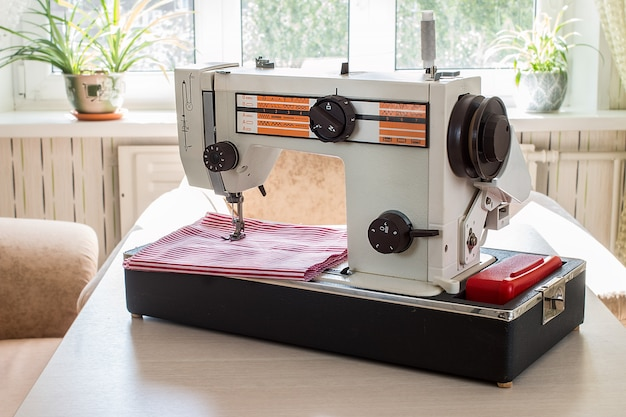 Macchina per cucire d'annata su una tavola di legno