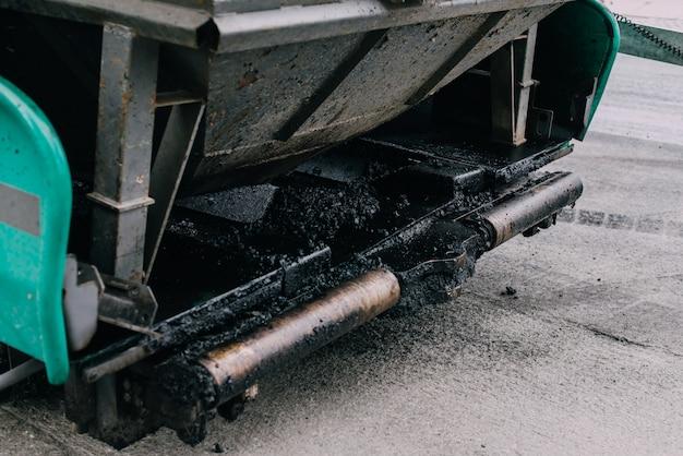 Macchina per la pavimentazione che pone asfalto o bitume fresco sopra la base di ghiaia durante la costruzione della strada principale. nuova strada
