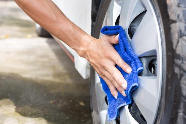Macchina per la pulizia dell'uomo con un panno in microfibra - dettagli auto e concetti di valorizzazione