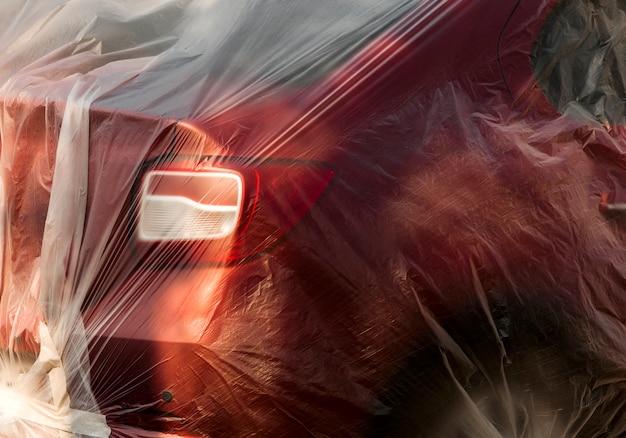 Macchina rossa avvolta in un film di cellophane.