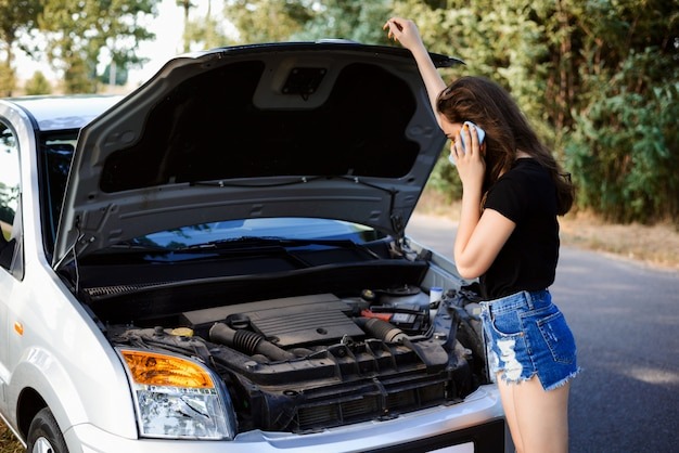 Macchina rotta a bordo strada. la ragazza chiama il servizio auto per portare la sua auto alla stazione di riparazione