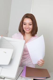 Macchina sorridente di funzionamento della fotocopia della donna di affari in ufficio