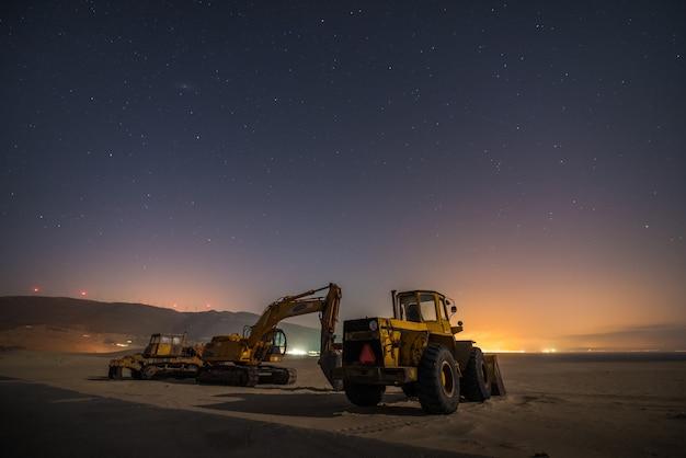 Macchine da lavoro su una duna di sabbia del sud della spagna durante la notte