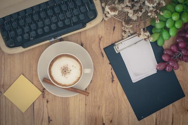 Macchine da scrivere e tazza di caffè d'annata sulla tavola di legno.