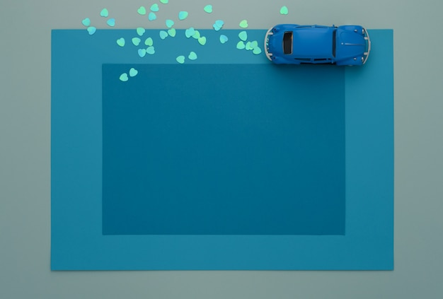 Macchinina blu su alcuni strati incornicia il fondo della carta blu.