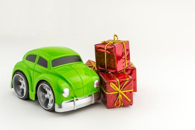 Macchinina verde giocattolo e piccole scatole regalo.