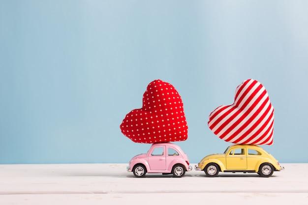 Macchinine rosa e gialle in miniatura che trasportano cuscini a forma di cuore