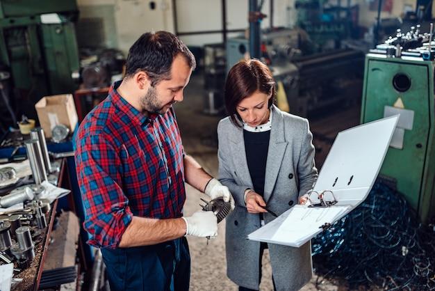 Macchinista che sta con l'ingegnere femminile e che misura il diametro della ruota dentata