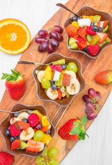 Macedonia di frutta con bacche fresche, arancia, cocco, mango e fette di banana