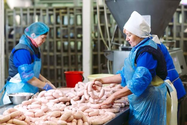 Macellai che trasformano le salsiccie alla fabbrica della carne.