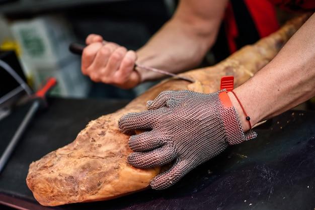 Macellaio che disossa un prosciutto con un guanto di sicurezza in rete metallica