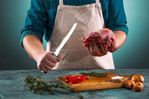 Macellaio che taglia la carne suina sulla cucina