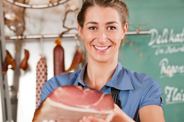 Macellaio donna o donna con prosciutto crudo in macelleria