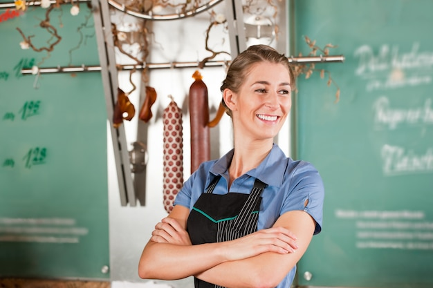 Macellaio donna o donna nel negozio di macelleria
