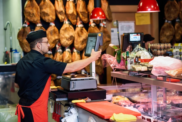 Macellaio in una macelleria che appesantisce la carne e carica