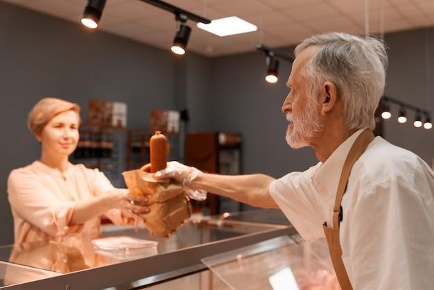 Macellaio senior che dà le salsiccie alla signora.