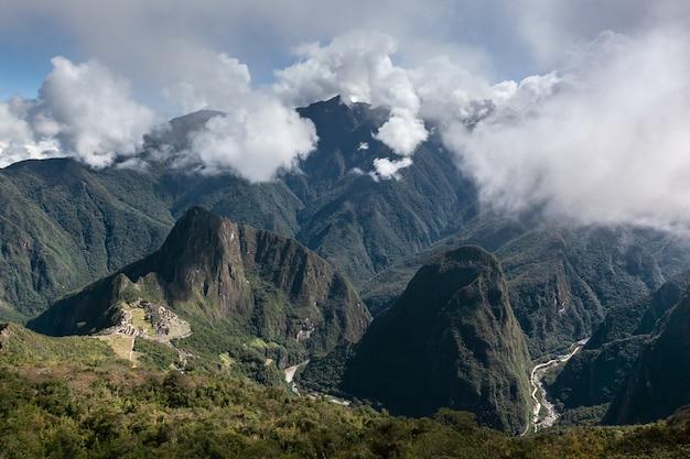 Machu picchu circondato dalle verdi colline delle ande e del fiume urabamba