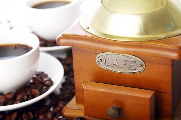 Macinacaffè anziano con la tazza bianca