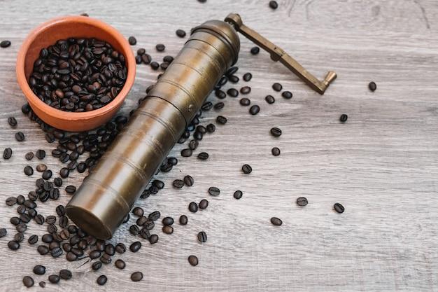 Macinacaffè e scodella con chicchi di caffè