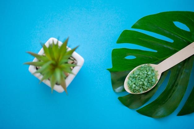 Macinazione del sale marino sul cucchiaio di legno della tabella misera blu-chiaro di legno