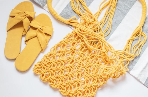 Macramè giallo fatto a mano, telo mare, sandali su bianco