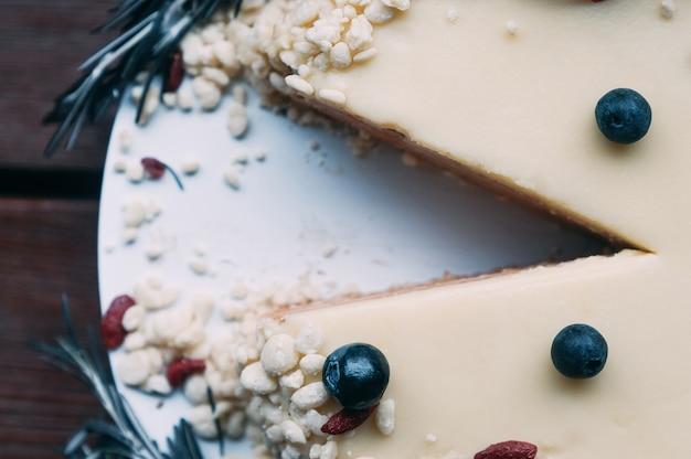 Macro torta del fuoco selettivo con la glassa bianca delle bacche