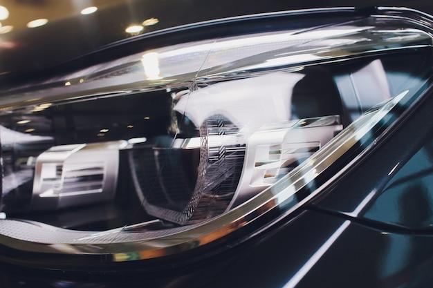 Macro vista del faro blu moderno della lampada del xeno dell'automobile.