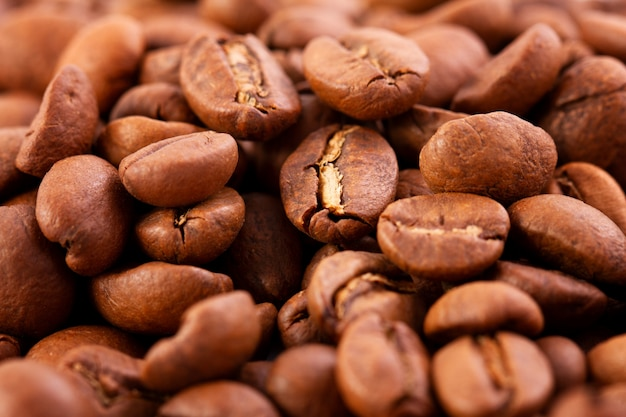 Macrofotografia di chicchi di caffè, la trama di chicchi di caffè. chicchi di caffè tostati su uno sfondo scuro