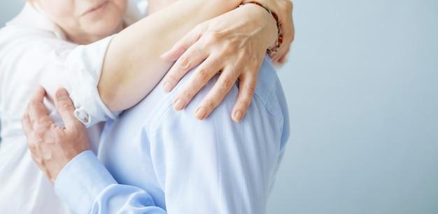 Madre abbraccia suo figlio, abbracci ravvicinati di uomo e donna, mani anziane, muro grigio blu, ruolo emotivo di genere maschile, malato da solo