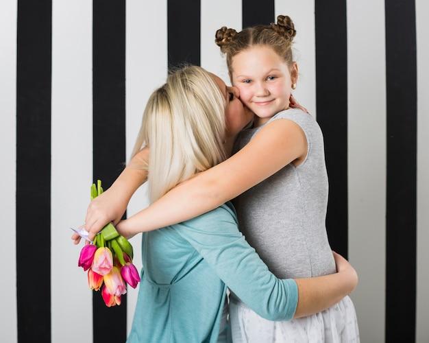 Madre abbracciare e baciare la figlia