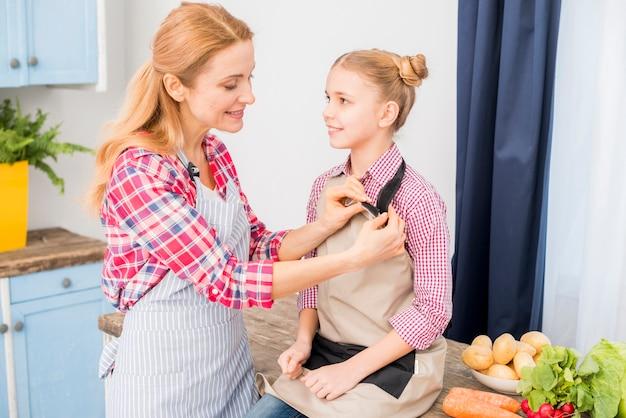 Madre aiutare sua figlia a indossare il grembiule in cucina