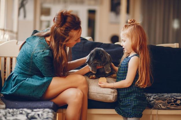 Madre alla moda con i capelli lunghi e un vestito verde che giocano con la sua piccola e carina figlia