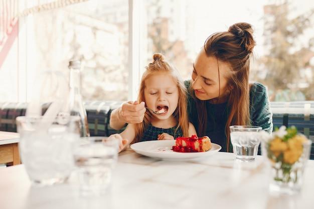 Madre alla moda con i capelli lunghi e un vestito verde seduto con la sua piccola figlia carina
