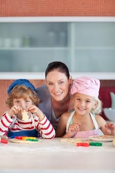 Madre allegra che cuoce con i suoi bambini