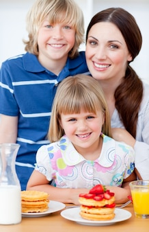 Madre allegra ed i suoi bambini che mangiano le cialde con le fragole