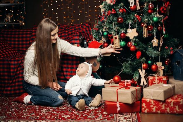 Madre amorosa che decora l'albero di natale con il bambino