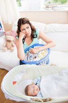 Madre annoiata che aspetta il suo bambino per svegliarsi seduto nel divano con il suo cesto della biancheria