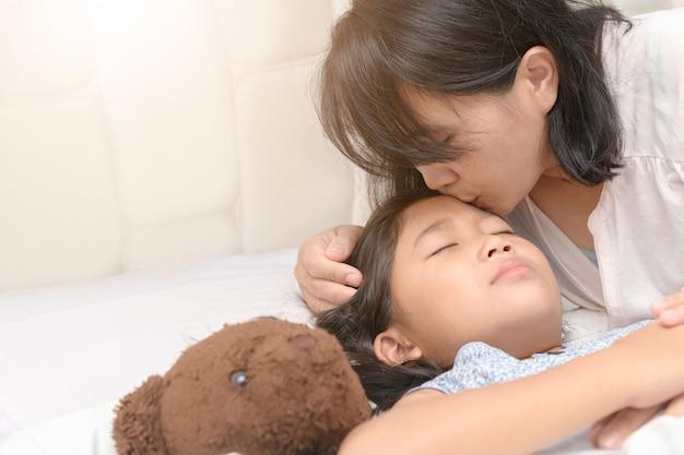 Madre asiatica amorosa che bacia delicatamente la figlia sveglia del bambino che desidera buona notte