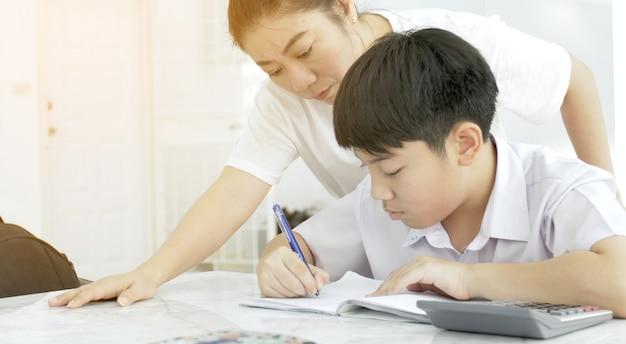 Madre asiatica che aiuta suo figlio a fare i compiti sul tavolo bianco.