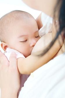 Madre asiatica che allatta al seno la sua neonata