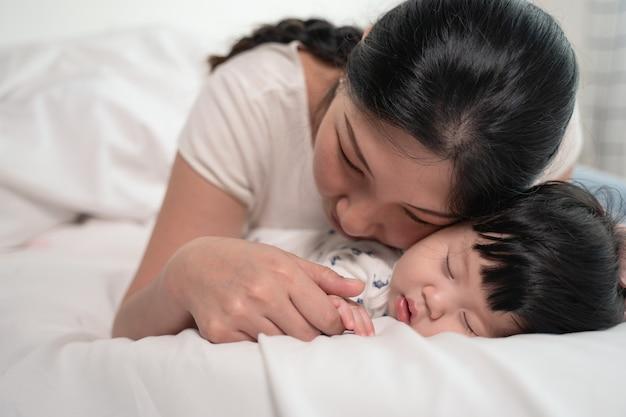 Madre asiatica che bacia e tocca un bambino che dorme sul letto con delicatezza e amore