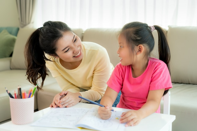Madre asiatica che gioca con sua figlia che riunisce le matite di colore alla tavola in salone a casa. concetto di espressione genitorialità o amore e legame.