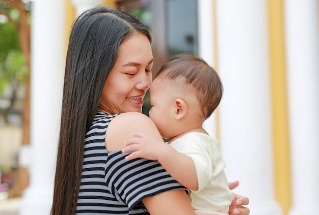 Madre asiatica che porta il suo bambino. avvicinamento.