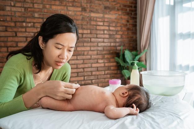 Madre asiatica che pulisce piccolo bambino dell'ombelico