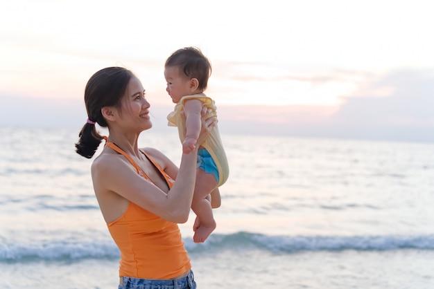 Madre asiatica che sta sulla spiaggia che tiene il suo bambino in due armi che alzano il bambino e che esamina il suo bambino.